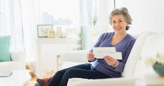 Mature woman holding bills | Tetra Images/Getty Images