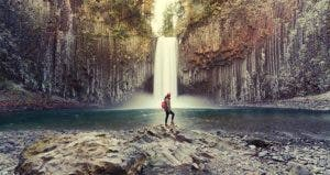 Woman standing by waterfall | Peerasith Patrick Triratpadoongphol/Shutterstock.com