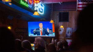 Crowd in a bar watching Donald Trump in a political debate