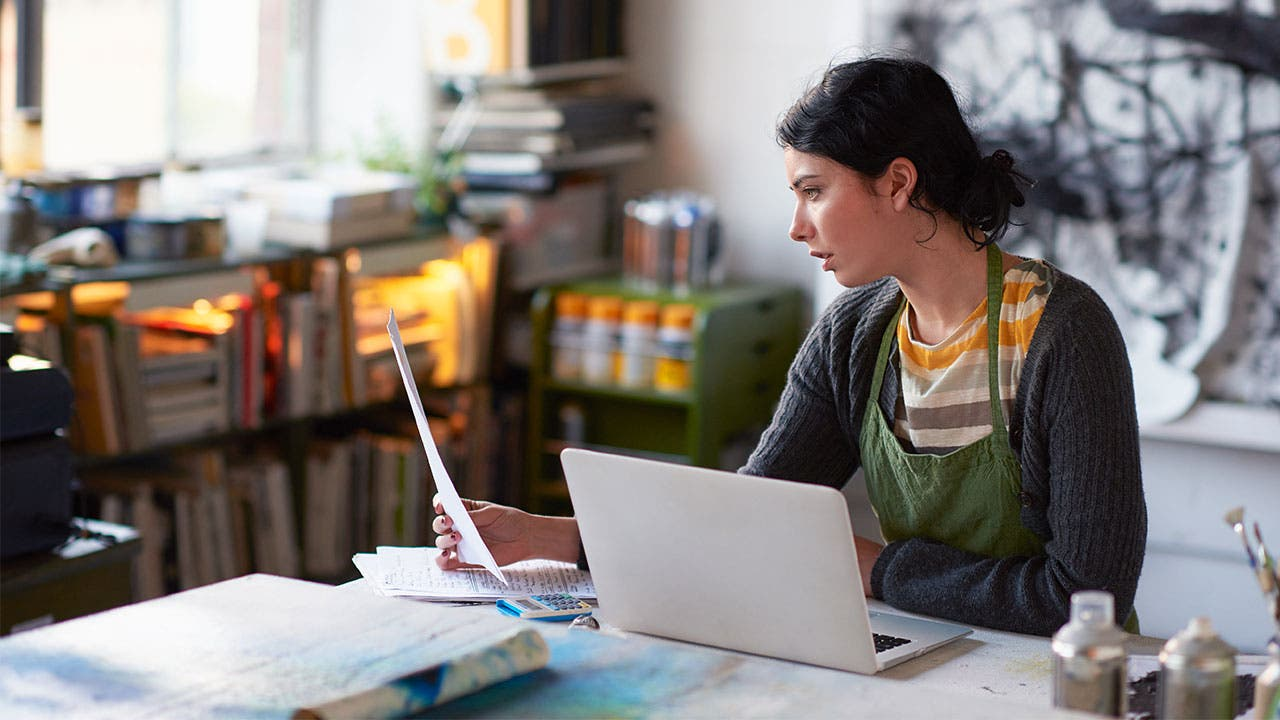 Woman reading papers and laptop