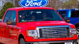 Family drives away from car dealership with a new truck