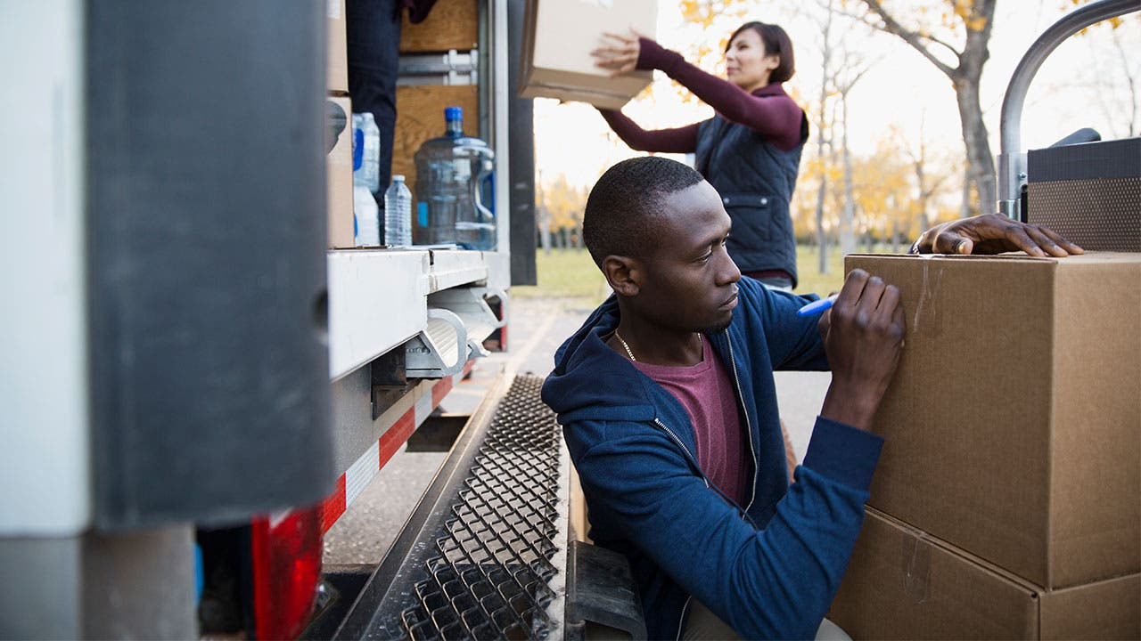 Man and woman packing boxes into moving truck