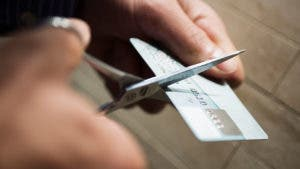 Man cutting credit card with scissors