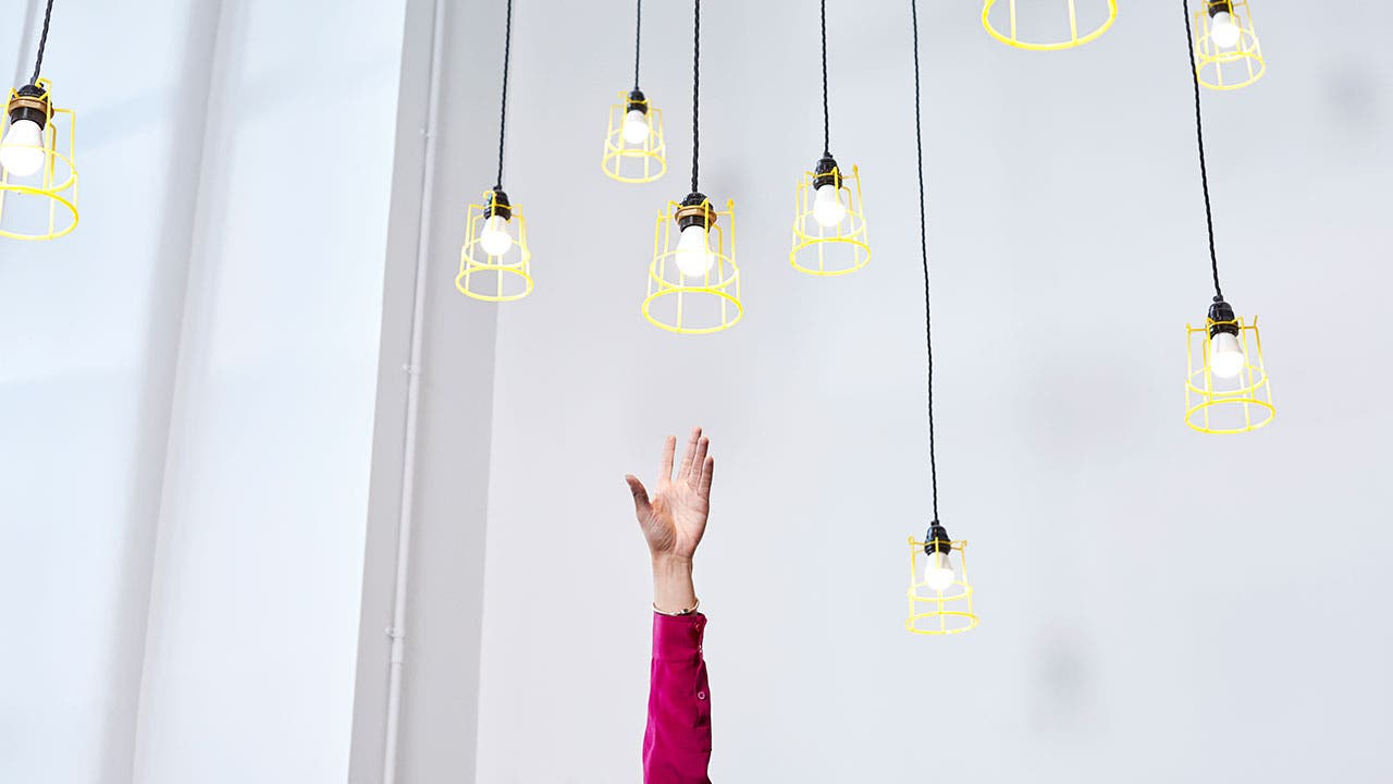Woman reaching for light bulbs out of reach