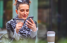 Young woman in the city using her credit card and a smartphone for an online transaction