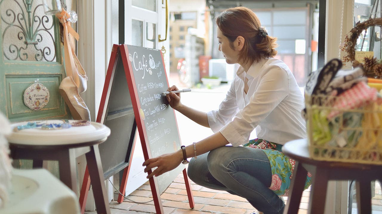 Woman in cafe writing on sign