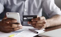 Man paying bill with credit card and phone