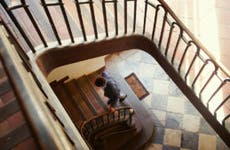 Man walking up spiral staircase