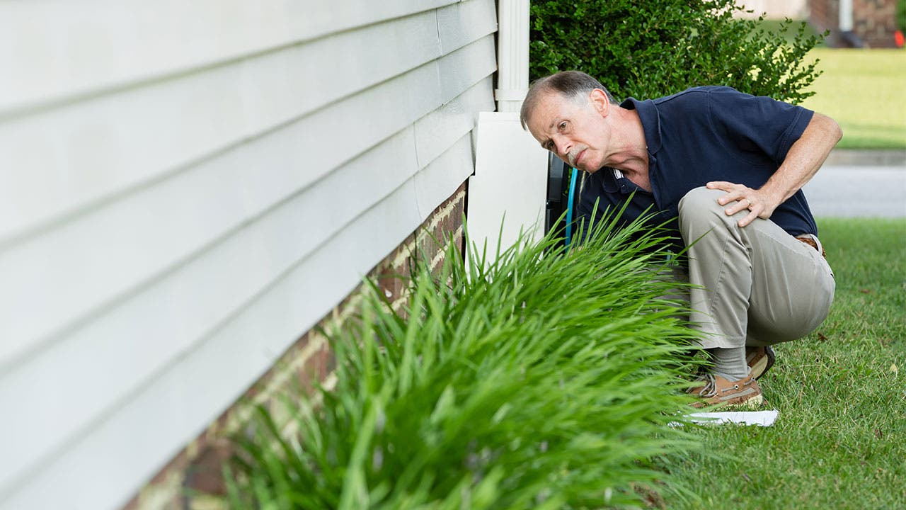 Man inspecting foundation of house