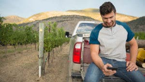 Man sitting in truck bed looking at phone