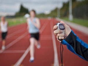 Person running on track and another person holding timer