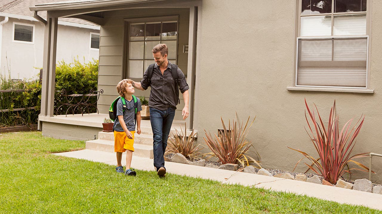 Father and son walking out of house