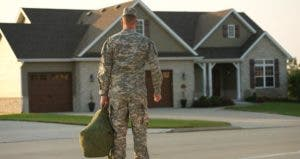 Military man wearing fatigues standing outside of his home