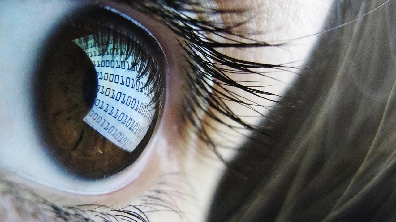 Close up of eye reflecting binary numbers