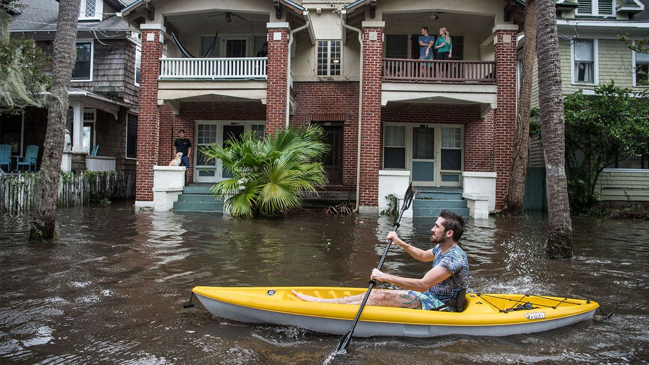 Man in Jacksonville paddles through flooding