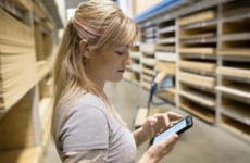 Woman in a hardware store using an app