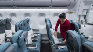 Flight attendant arranging pillows before flight