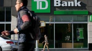 People walking by TD Bank