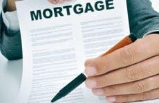 Man holding pen to mortgage contract © Marius Pirvu/Shutterstock.com