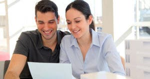 Smiling young couple holding a paper © goodluz - Fotolia.com
