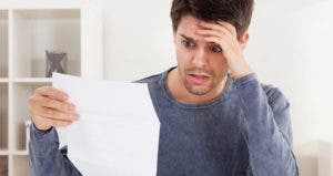 Young man looking at paper in panic © Andrey_Popov/Shutterstock.com