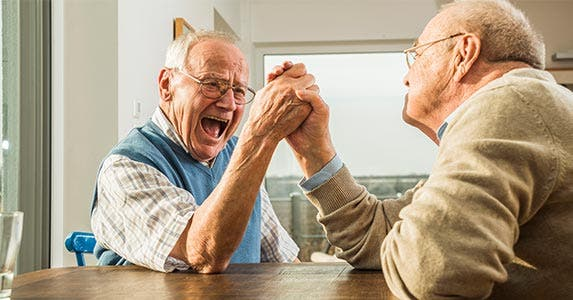 Two elderly men arm wrestling
