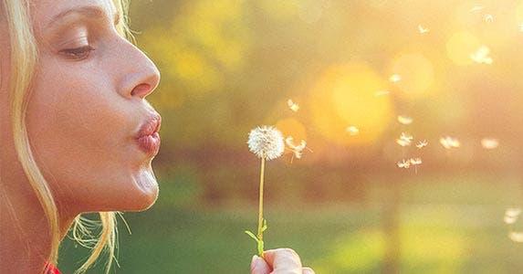 Woman blowing a dandelion