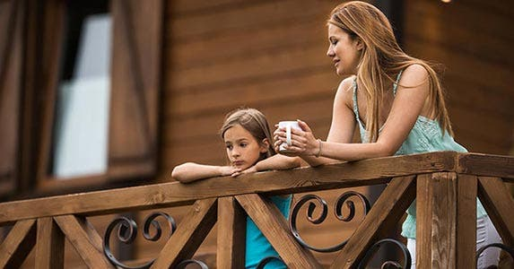 Mother and daughter talking outside on house deck