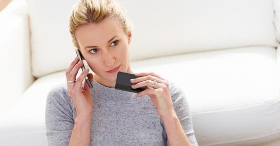 Woman leaning on white sofa holding credit card on the phone © iStock