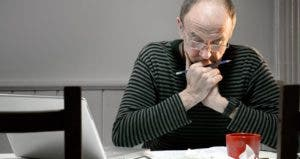 Man working on finances in his kitchen © iStock