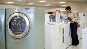 Woman looking at washing machines in appliance store