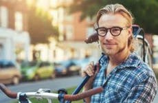 Young man in plaid shirt holding bike © Uber Images/Shutterstock.com