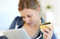 Woman reading tablet while holding a credit card  © goodluz / Fotolia