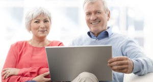 Retired couple on couch holding tablet © Kinga / Shutterstock.com