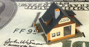 Miniature house on a $100 bill © Guy Shapira/Shutterstock.com
