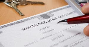 Person reviewing mortgage loan agreement on a desk © NotarYES/Shutterstock.com