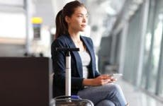 Young woman sitting in an airport waiting to board a plane © Maridav/Shutterstock.com