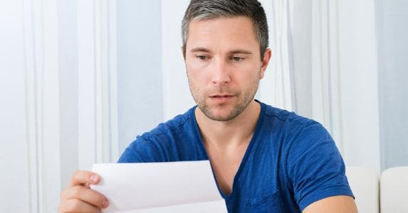 Man unhappily looking at a piece of paper © iStock