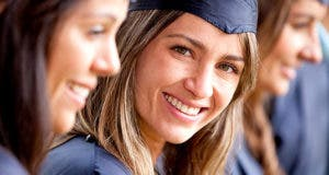 Beautiful female graduate standing out from a group of students smiling © Andresr/Shutterstock.com