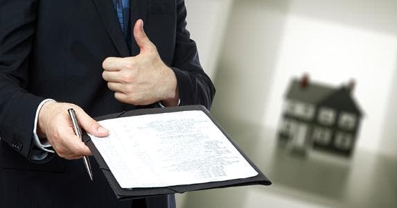 Loan officer holding paperwork and thumb up © iStock