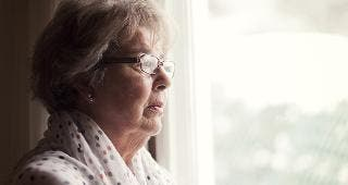 Senior woman standing by window © Nadino/Shutterstock.com
