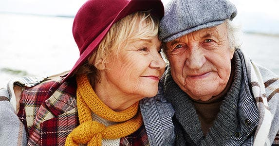 Elderly couple wearing hats and scarves