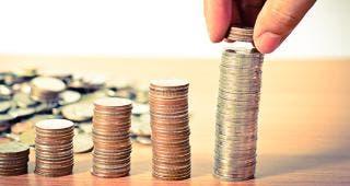 Hand stacking quarters © Singkham/Shutterstock.com