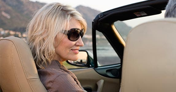 Woman wearing sunglasses driving convertible