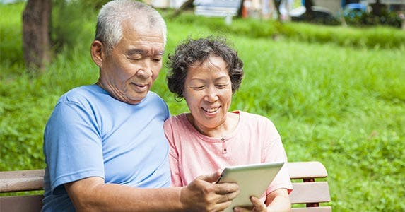 Man and woman sitting on park bench looking at tablet