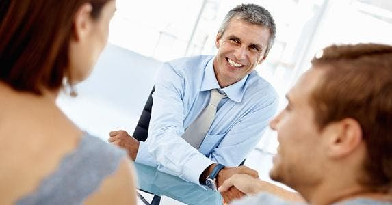 Adviser shaking hands with couple clients