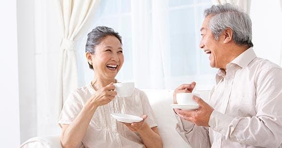 Man and woman laughing, drinking tea