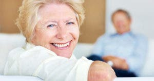 Senior woman smiling on couch © iStock