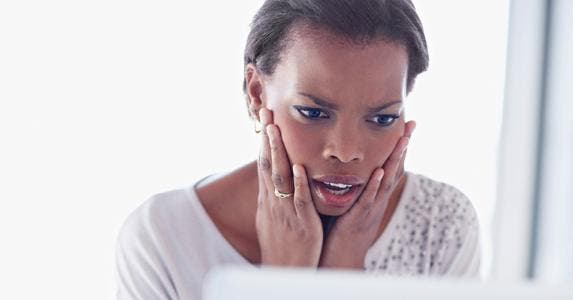 Shocked woman looking at her computer screen © iStock