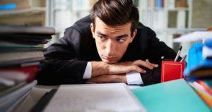 Young male office employee sitting bored at work © iStock